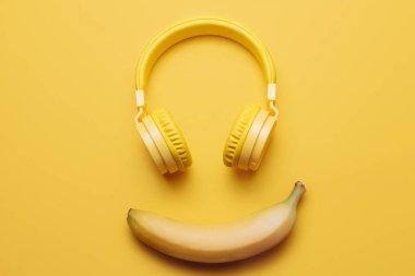 Yellow headphones on yellow background. Music concept.