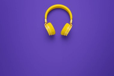 Yellow headphones on purple background. Music concept.
