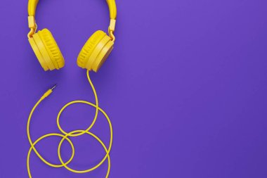 Yellow headphones on purple background. Music concept.