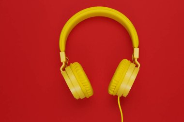 Yellow headphones on red background. Music concept.