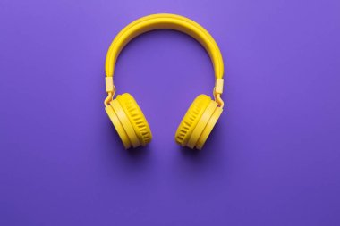 Yellow headphones on purple background. Music concept
