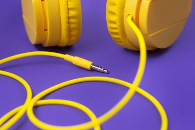 Yellow jack plug cable and headphones on purple background. Music concept.