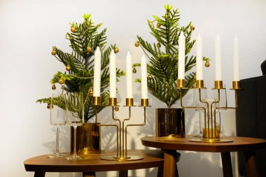 New year's interior. A small artificial Christmas tree with toys and candles. Glasses serving