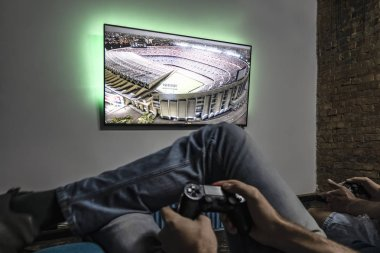 Kiev, Ukraine, September 19, 2018: Two men playing video game. Hands holding console controller. Football or soccer game on the television. Widescreen tv hang on the wall