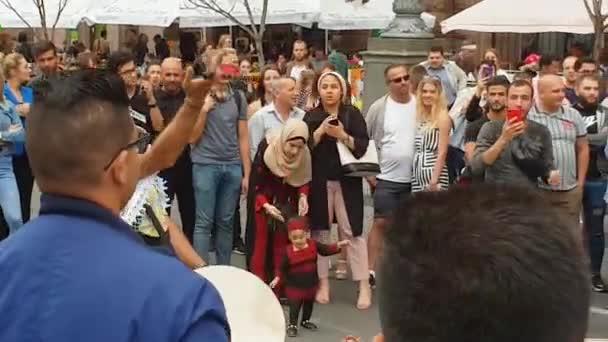 Ukraine, Kiev, September 9, 2018: random men dance on Khreshchatyk Street. Bearded man with a drum is spinning in the center of a circle. Celebration. Turkish community.