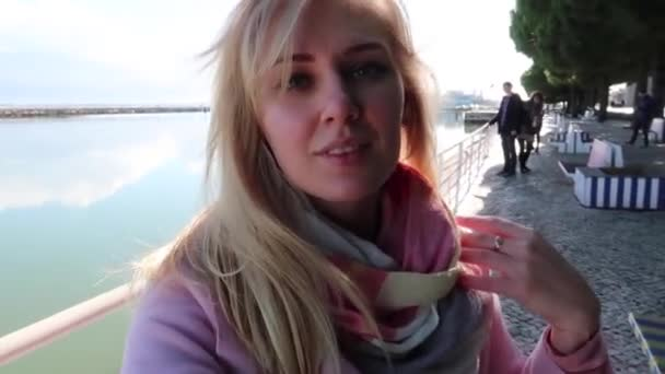 Beautiful blonde woman having video chat using smartphone outdoors sharing travel adventure friends showing beautiful landscape background and ocean. Girl filming selfie video for social media. Portugal vacation. Slow motion