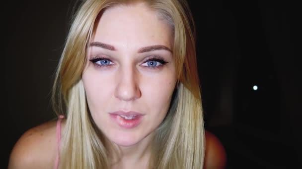 Close-up Portrait eine sexy schöne junge blonde Frau mit strahlend blauen Augen, sie schaut in die Kamera mit einem verführerischen Blick und beißt sie Lippe, flirten