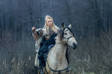Blonde warrior woman riding a horse with ax in hand. Viking woman ready to attack, movie theme.