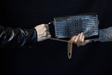 Adam bir kadın, siyah bir arka plan elinde bir çanta kapmak