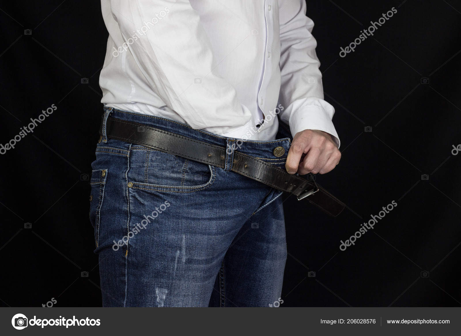 A man in a white shirt and jeans thrust his hand into his