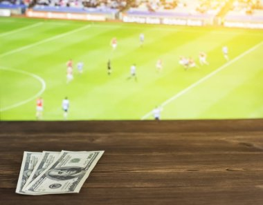 Money dollars on the background of the TV on which show Gaelic football, sports betting, dollars, Gaelic Football