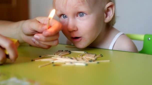Matka světla na zápasy a učí malé dítě, které nemůže vzít děti odpovídá, následky požáru, dítě fouká na zápas, nebezpečné