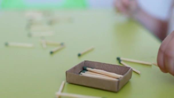 Malé dítě si hraje s zápasy na stůl, bílé pozadí, Kavkazský, nebezpečí, ruce dítěte, detail