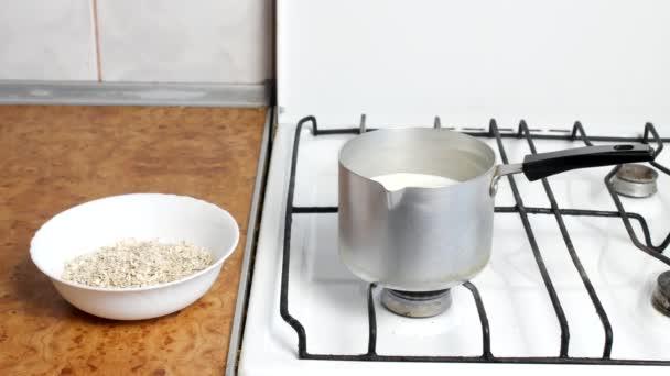 Vaření, ovesné vločky, vařící mléko a ovesné vločky v talíři, detail