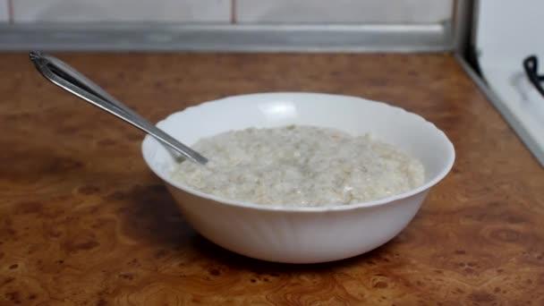 vaření ovesných vloček, Žena nalévá cukr sladový ovesné vločky, zblizka, snídaně