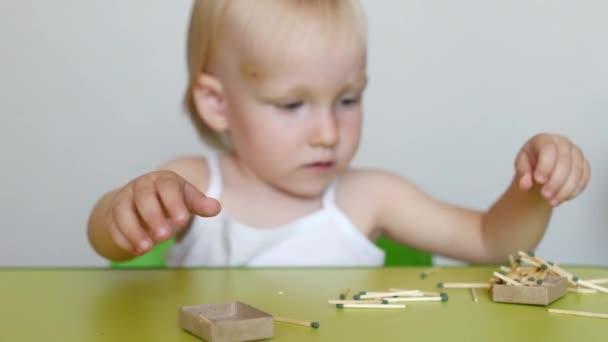 Malá holka si hraje s zápasy, uspořádá zápasy v krabičce od sirek, detail, nebezpečí, děti a oheň, Kavkazský, nebezpečí požáru