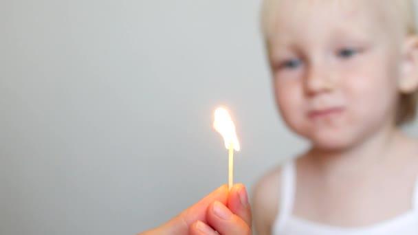 malá holčička sfoukne hořící zápalkou, close-up, nebezpečí požáru, děti a oheň, Kavkazský