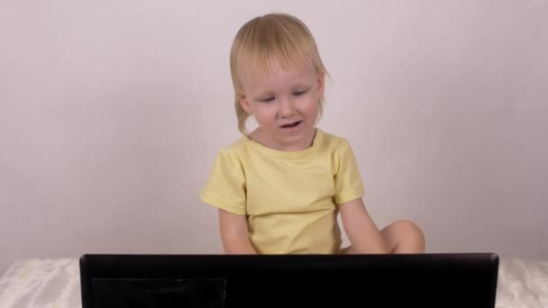 Little smiling blonde girl presses the buttons on the laptop and looks into the computer, relaxation