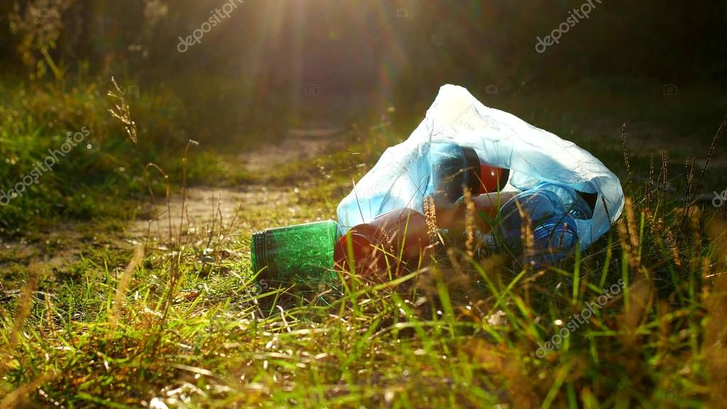 A package of plastic garbage lies in the forest on a forest road, pollution of nature, garbage and nature, the sun, close-up, rubbish