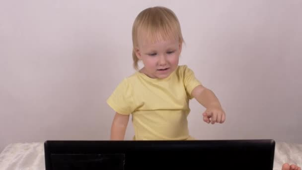 Little caucasian girl plays and plays with computer laptop, emotions