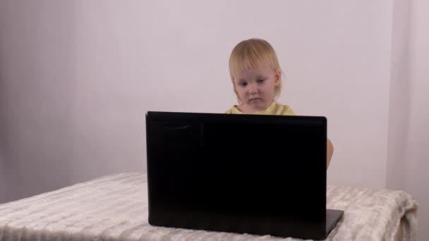Kavkazské holčička hraje a hraje si s počítači laptop, emoce, 4k