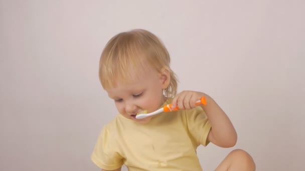 Beautiful caucasin little girl brushing her teeth and laughing on a white background, close-up, slow mo