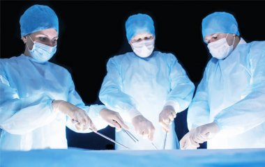 Three surgeons, a man and a woman, perform surgery in the operating room to remove and transplant human organs, resect the stomach and remove the gallbladder, appendicitis