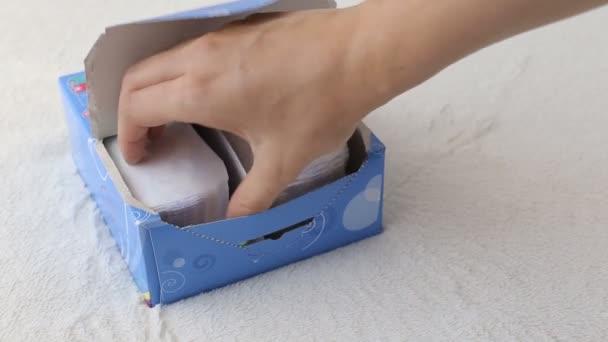 Mädchen öffnet eine Schachtel mit täglichen Damenbinden und nimmt eine, in Großaufnahme, Damenserviette