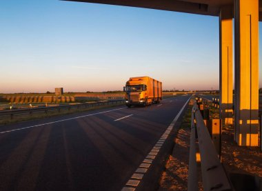 A yellow road train carries cargo against the backdrop of a sunny sunset and blue sky. Concept of work as a truck driver on a cadence, background