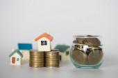 Mini-Haus auf Stapel von Münzen, Geld und Haus, Immobilieninvestitionen, Geld sparen mit Stapel von Münzen, Hypothekenkonzept, isoliert