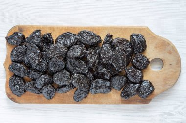 Dry prunes on rustic wooden board on a white wooden table, overhead view. Close-up. Flat lay, from above, top view.