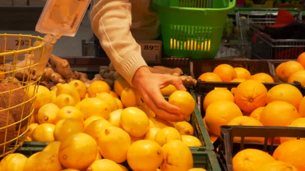 Young guy chooses lemons in a supermarket, a hand puts a lemon in a grocery green basket. Healthy food, fruit. 4K footage