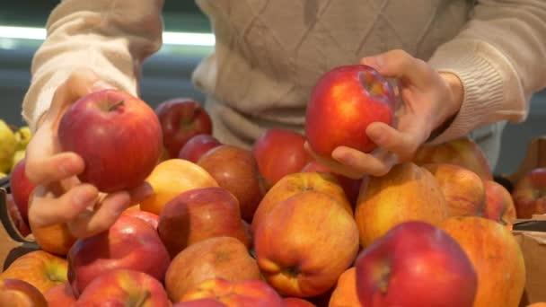 Mladý muž se rozhodne jablka v supermarketu. Ruku se ujímá červené jablko z obchodu čítače. Zdravé jídlo. 4 k video