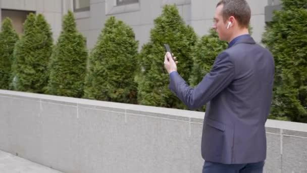 Ein junger Geschäftsmann läuft mit drahtlosen Kopfhörern in den Ohren und spricht per Videoanruf auf dem Smartphone. ein Mann im Anzug, der auf einer Videokonferenz spricht. 4k Filmmaterial
