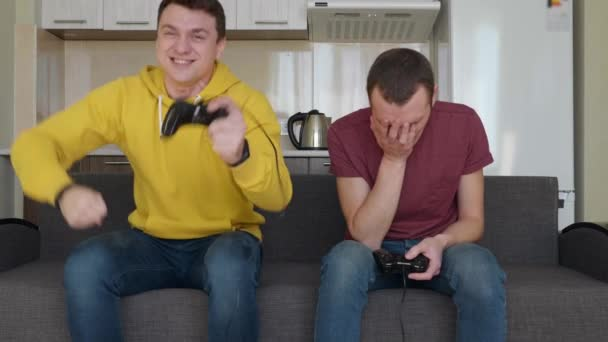 Two men are playing video game and win. Young guys are sitting on the couch, hold gamepads in their hands, play console, enjoy the victory, one of them rises from the sofa and performs a winning dance