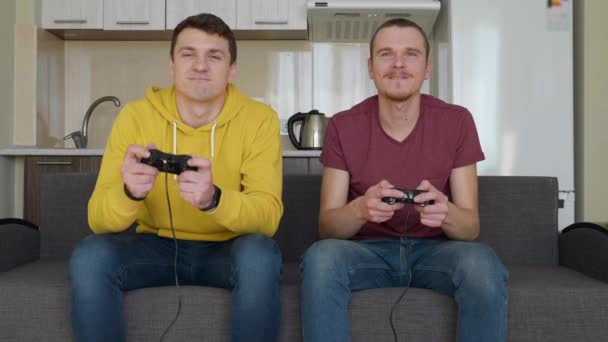 Two men are playing video game against each other. Young guys are sitting on the sofa, hold gamepads in their hands and play console, one of them wins and enjoy the victory, the second friend is upset