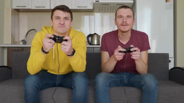 Two men enthusiastically play video game. Young guys are sitting on the couch, hold gamepads in their hands and play the console, actively move during the passage of one of the levels. Team match. 4K footage.
