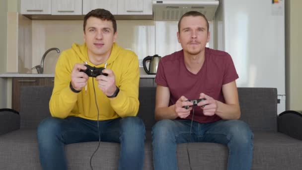 Two men are playing video games and lose. Young guys are sitting on the couch, hold gamepads in their hands and play console, discuss their mistakes during the passage of one of the levels. Team match. 4K footage.