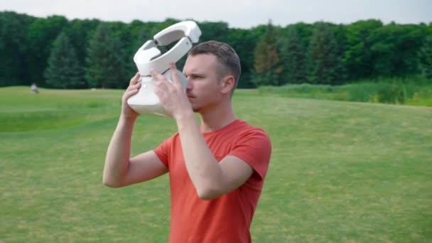 Ein Mann legt sich in einem Park ein Vr-Headset auf den Kopf und schaut sich um. Ein junger Mann in rotem T-Shirt und Helm erlebt virtuelle Realität vor dem Hintergrund der Natur. Dynamische Aufnahmen. 4k Filmmaterial.