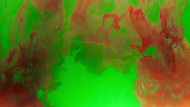 Colorful red ink mixing in water, swirling softly underwater with green ink on background. Colored acrylic cloud of paint isolated. Abstract smoke explosion animation. 4K footage.