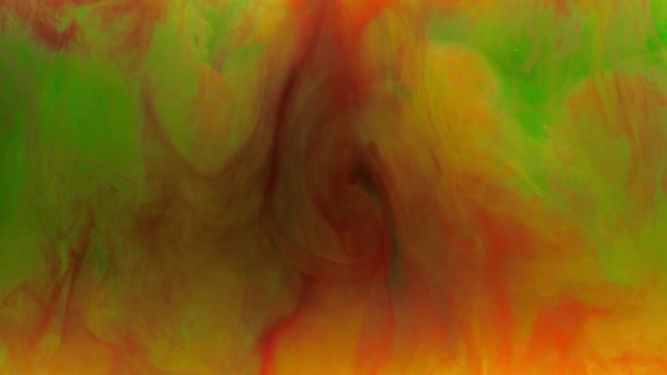 Colorful red and yellow ink mixing in water, swirling softly underwater with green ink on background. Colored acrylic cloud of paint isolated. Abstract smoke explosion animation. Slow motion. 4K footage.