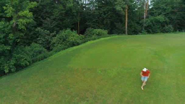 Letecký pohled na člověka, který používá náhlavní soupravu a hraje virtuální hru v parku. Mladý muž v helmě, který prožívá realitu na pozadí přírody. 4k bzukot záběr.