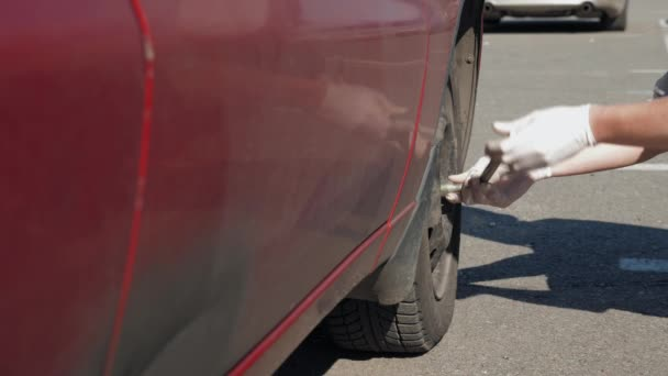 An inexperienced man in white gloves is trying to spin a wheel in his broken and dirty red car. Young guy repairing a car in outdoor. The car broke down on the road. Close-up. 4K footage.
