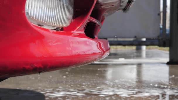 Voda a saponát se odvodní z červeného mycího vozu v samoobslužného mycím voze. 4k záběr.