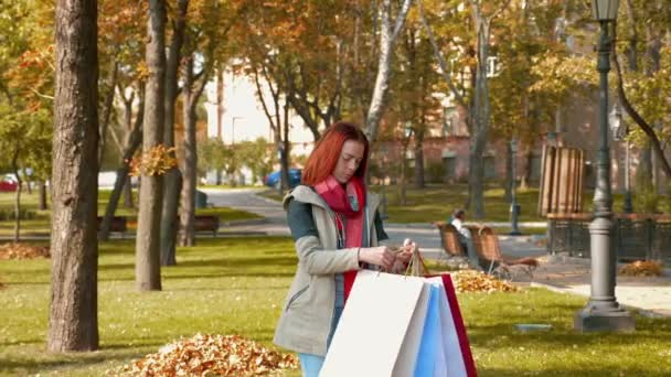 Young attractive red haired woman in a jacket is shopping. Happy girl with foxy hair runs through the park with purchases in multi-colored paper bags and rejoices. Sale, retail industry concept. 4K