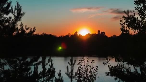 Čas zapadajícího slunce nad jezerem a lesem. Stromy proti modré a sluncem zlaté obloze. Mraky se rychle pohybují. Silueta smrku proti zapadajícímu slunci. Přirozené pozadí. Den za nocí. Záběry 4k.