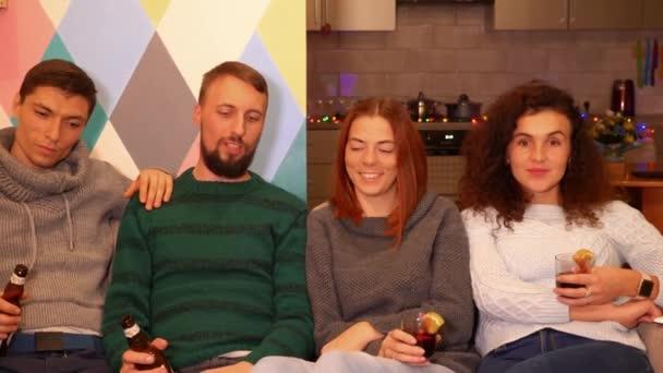 Šťastní přátelé sedí na gauči, pije alkohol a oslavuje novoroční večírek doma. Mnohobarevná světla, věnce na pozadí. Koncept svátků a oslav. Záběry 4k.