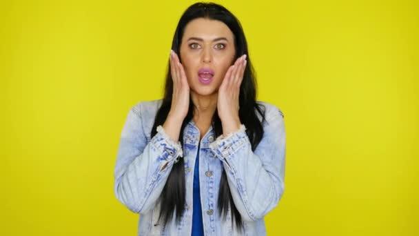 Frau schockiert über das, was sie mit Handflächen vor Wangen auf gelbem Hintergrund sah