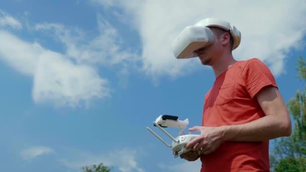 Mann steuert Quadrocopter per Fernbedienung