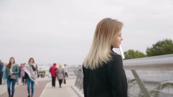Positive woman in jacket walks on pedestrian bridge turns to the camera, smiles